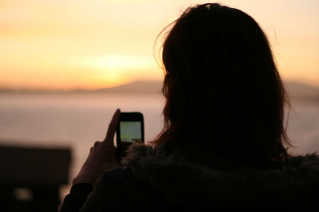 girl at sunset using app to repel mosquitoes